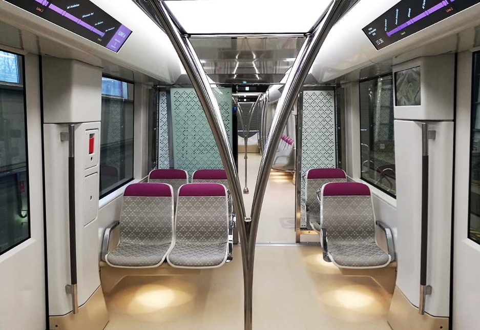 The interior of a Riyadh Metro carriage: the triangle pattern on the chairs is taken from the mud houses of Riyadh, while the vertical handrails resemble branching palm trees.