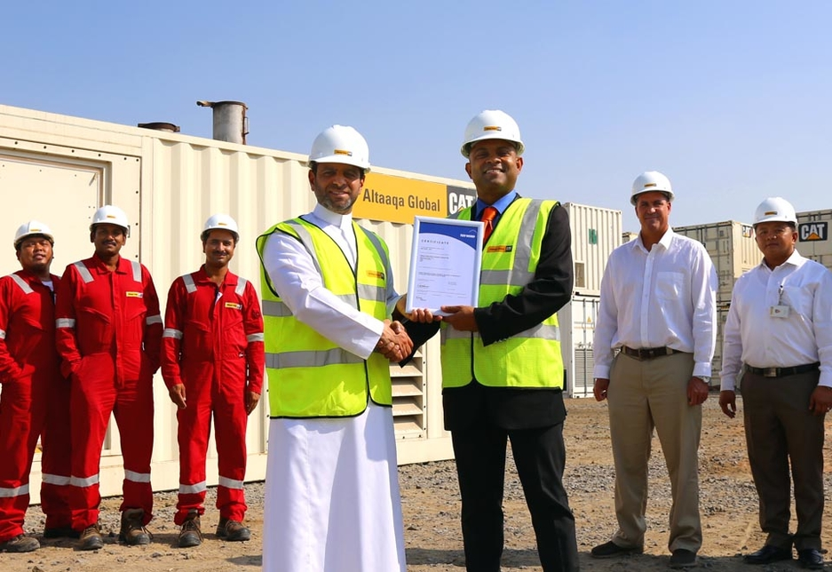 Majid Zahid, chief commercial officer for Altaaqa Global (L) is handed the ISO 50001 certification by Shibu Davies, GM for certification at TÜV Nord.