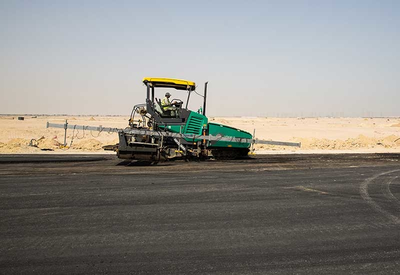 A Vgele paver equipped with a 14m-long averaging beam delicately lays asphalt for the Formula 1 subcourse on the Kuwait Motor Town project.
