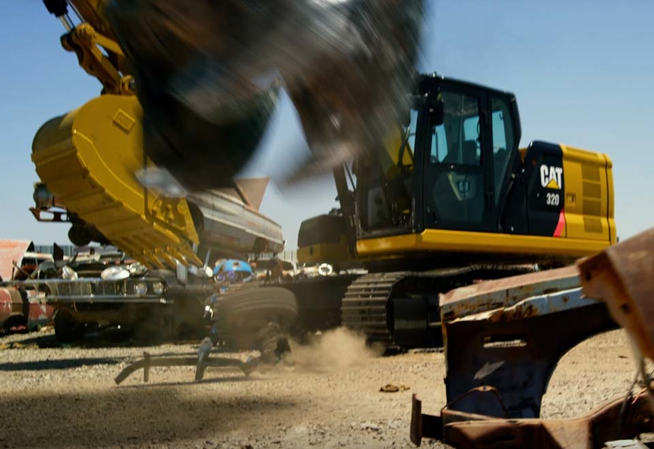 The foot of Grimlock, the Tyrannosaurus Rex-shaped leader of Dinobot, descends against the backdrop of a Caterpillar excavator.