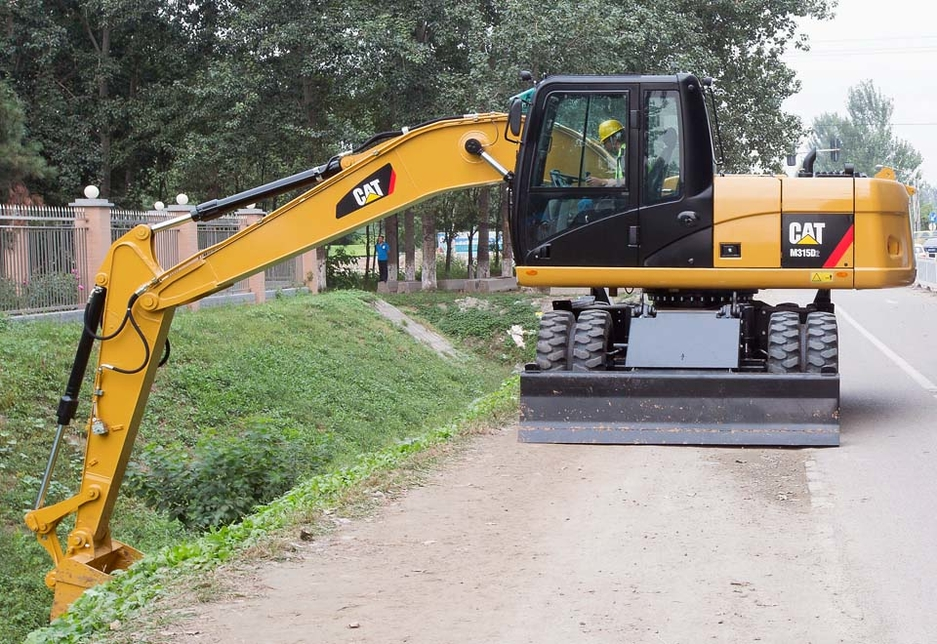 A Cat M315D2 wheel excavator performs work activities on an on-road site.