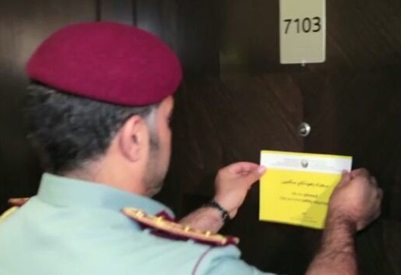 An officer fixes the welcome note on a door at the Torch Tower. [Image: Dubai Civil Defence Twitter]