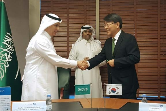 Saudi Arabia's Minister of Environment Water and Agriculture shake hands with Yoon Seok-won, VP of Doosan Heavy Industries, and after signing the construction contract.