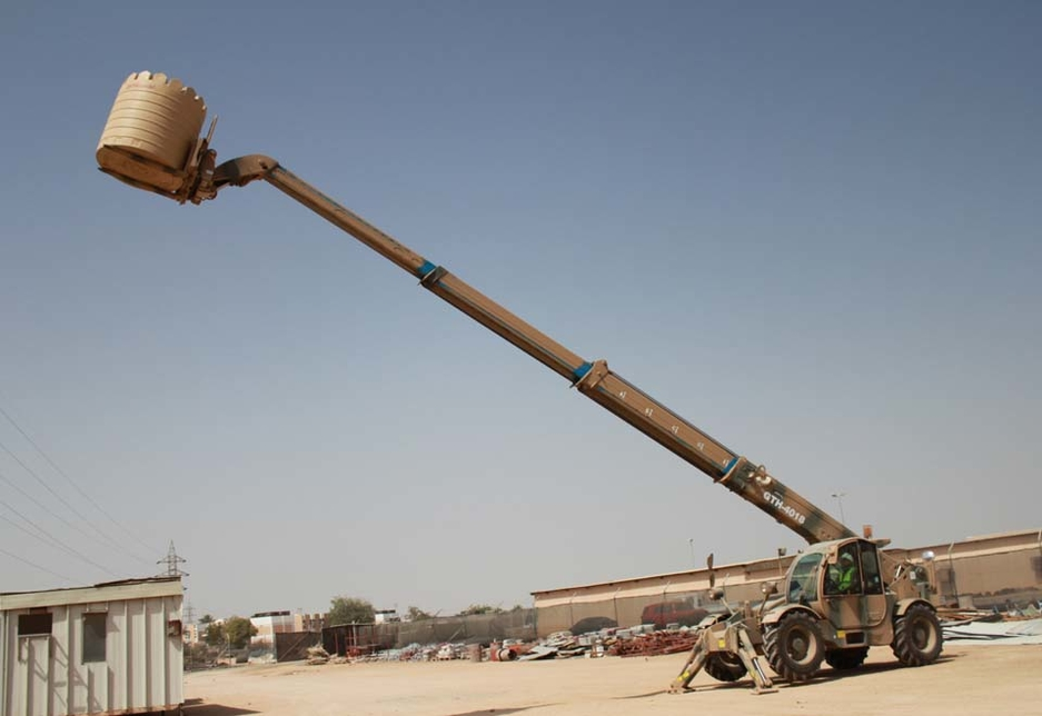 The custom livery Genie GTH-4018 telehandler lifts a water tank at its full horizontal reach of 13.36m in the Sultan of Omans Engineers equipment park.