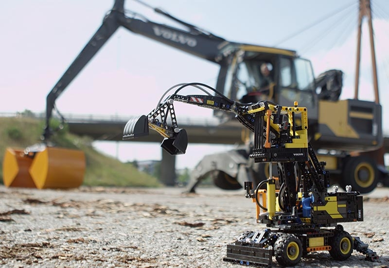 The 1:20 scale model Volvo EW160E wheeled excavator, against the backdrop of the full-scale machine.