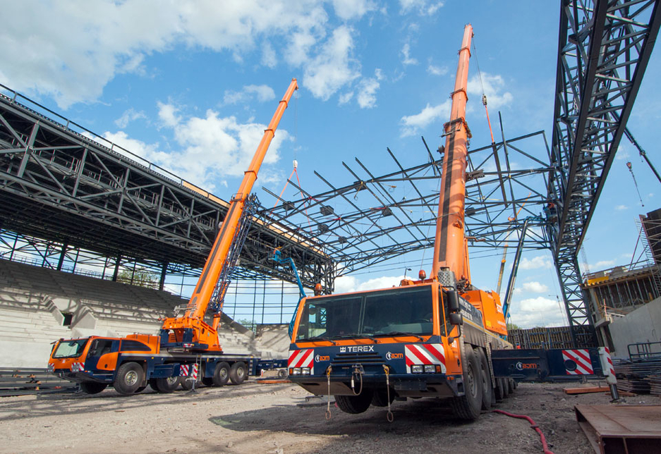 A Terex Explorer 5800 and Terex AC 250-1 pair of all-terrain cranes are used to tandem lift pre-fabricated steel roof structures into place during the construction of a sports venue.