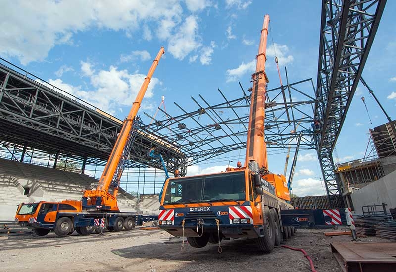 A Terex Explorer 5800 and Terex AC 250-1 tandem lift a pre-fabricated steel roof structure into place.
