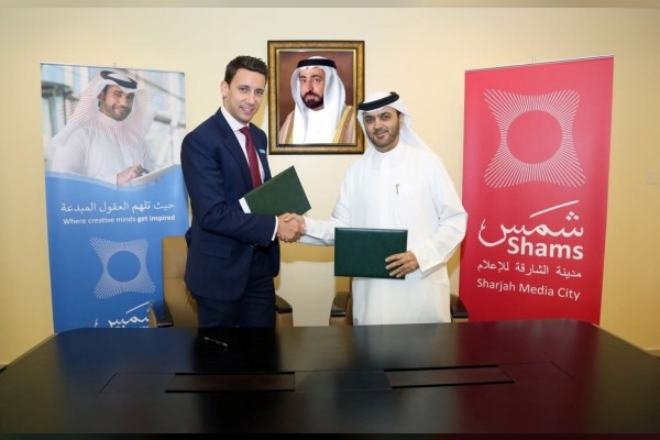 Dr. Khalid Omar Al Midfa and Steve Morgan shake hands after the deal signing ceremony.