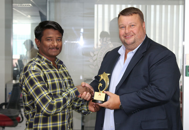 Nisham Kunnath Valappil (left) received a trophy from Greg Ward, managing director at Transguard Group (right).