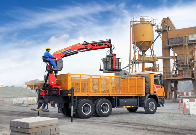 A truck equipped with a flat-bed body and a rear-mounted Palfinger knuckle-boom loader crane.