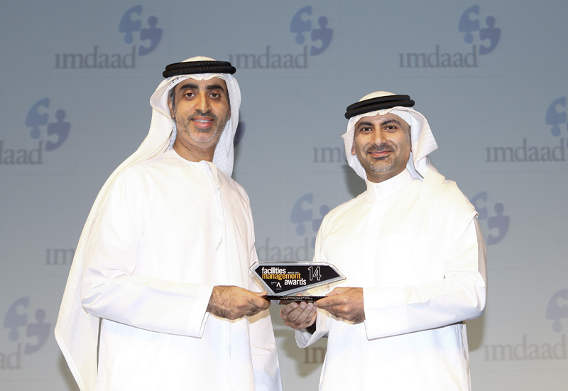 """Bee'ah's Group CEO Khaled Al Huraimel receiving the """"FM Executive of the Year"""" trophy from Imdaad COO Mahmood rasheed at the 2014 fmME Awards."""