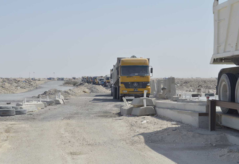 A line of trucks arrive at the site with construction waste to be recycled.