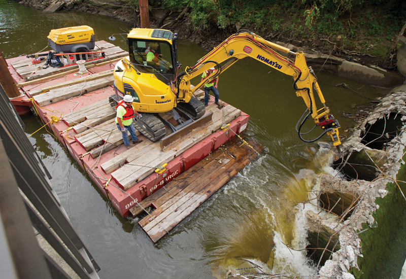 RiverReach used an Atlas Copco SB 552 breaker, a Komatsu mini excavator, and a modular barge to demolish the Sheraton Mill Dam.