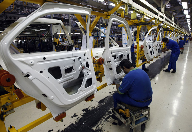 Iranian technicians work on parts for Peugeot 206 cars at the Iran Khodro auto plant, west of Tehran.