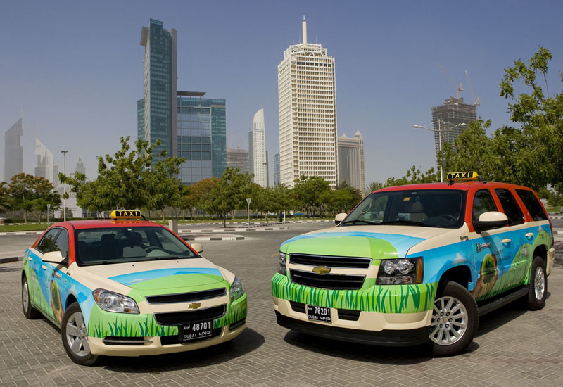 Hybrid Dubai taxis emblazoned with green livery.