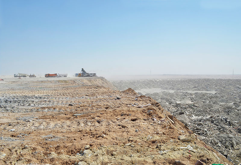 Like a vast moonscape, Rawdat Rashid landfill for construction debris stretches to the horizon, while an endless stream of trucks dump their cargo int