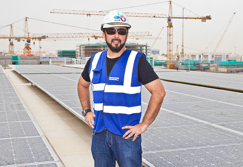 Manos Kappas stands amid the solar array on the DI Annex building Msheireb. A total of 1,550 solar panels stretch over the roof, producing 340kW peak