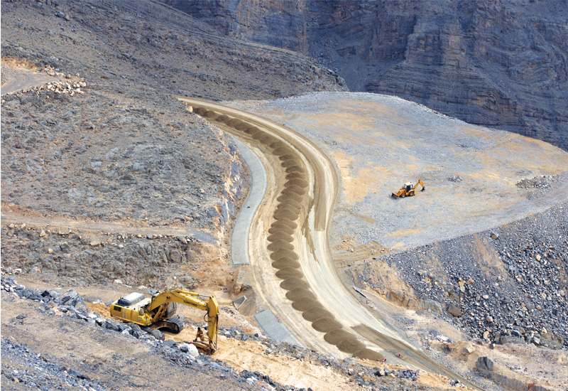 Piles of aggregate waiting to be compacted that have been trucked from the crusher at the top of the hill. To the right, a JCB sits on a plateau creat