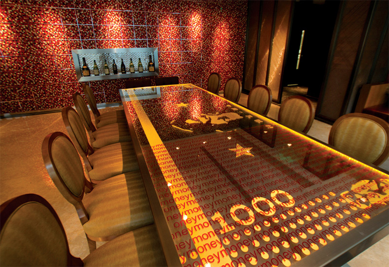 The private dining room features a glass table imprinted with a Chairman Mao 1000RMB note.