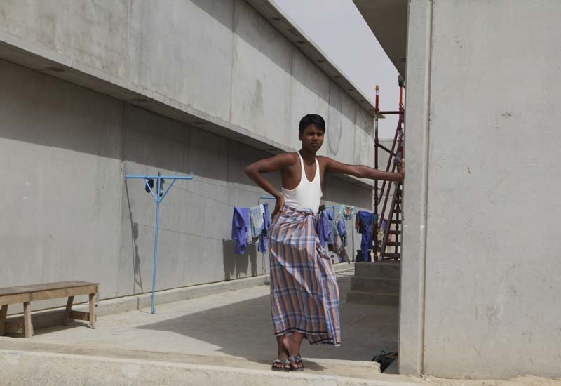 A worker stands outside a building at Nad al Sheba labour camp.