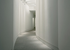 A subtly lit winding corridor by Flos.