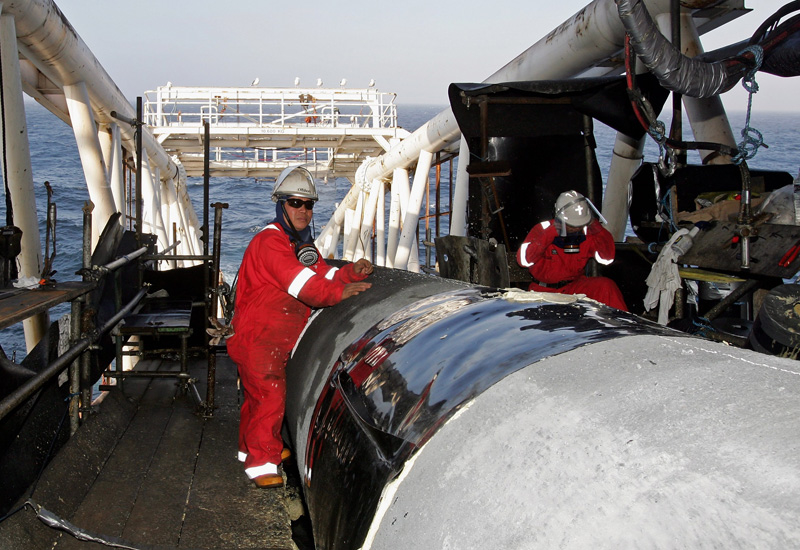 Workers make final preparations to pipes, as they enter the sea from the pipelay vessel Acergy Piper, to form part of the 1200km Langeled pipeline.
