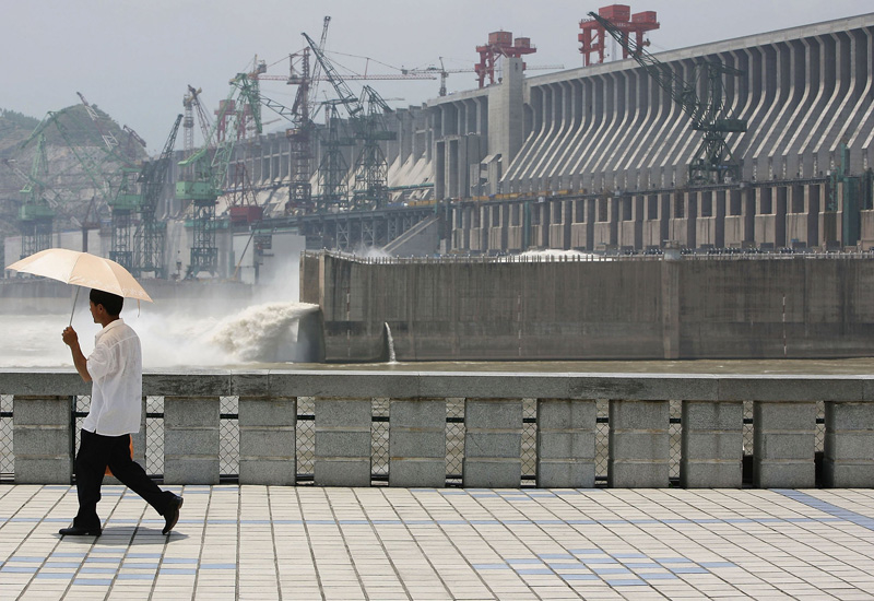 A tourist walks in front of the controversial Three Gorges Dam (Andrew Wong/Getty Images).