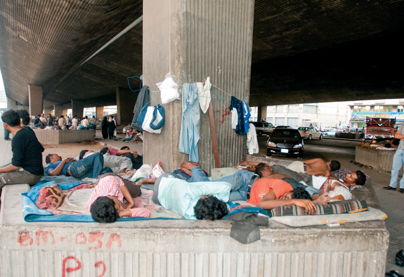 Illegal migrant workers rest in the early hours of the morning, hoping for a ministry van to come round and pick them up for deportation.