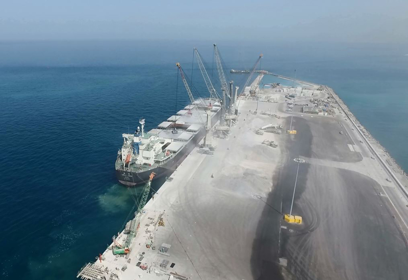 An aerial view of ship loading work at Saqr Port [image: Bam International].