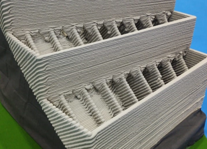 TAM's 9-axis 3D printer can print concrete in angular motions in a way that it is travelling up and down in slopes